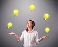 Señora joven que se coloca y que hace juegos malabares con las bombillas Imagenes de archivo