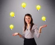 Señora joven que se coloca y que hace juegos malabares con las bombillas Imagen de archivo libre de regalías