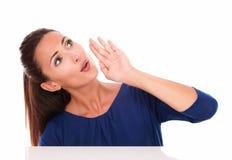 Señora linda en la camisa azul que mira para arriba mientras que habla Fotos de archivo libres de regalías