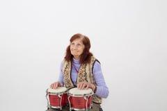 Señora mayor divertida que juega el bongo Fotos de archivo libres de regalías