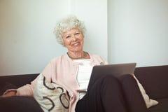 Señora mayor feliz en casa con el ordenador portátil Foto de archivo libre de regalías