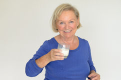 Señora mayor sana que bebe la leche fresca Foto de archivo