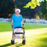 Señora perjudicada mayor con un caminante en un parque Fotos de archivo