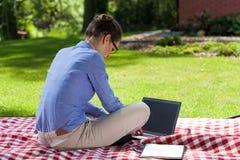 Señora que trabaja en el ordenador en jardín Fotos de archivo