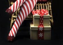 Señora Santa del tema de la Navidad con las piernas y los regalos rojos y blancos de la media de la raya del bastón de caramelo Foto de archivo libre de regalías