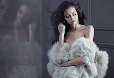 Señora sensual que presenta al lado del espejo Imagen de archivo libre de regalías