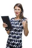 Señora sonriente en un vestido impreso elegante que sostiene una tableta Imagen de archivo libre de regalías