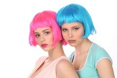 Señoras en pelucas coloridas y la presentación de las camisetas Cierre para arriba Fondo blanco Fotos de archivo