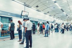 SEOUL, KOREA - AUGUST 12, 2015: Lots of people standing in the line on a subway platform and patiently waiting for their train to. SEOUL, KOREA - AUGUST 12, 2015 Stock Photo