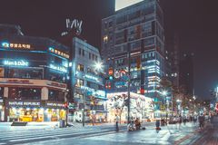 SEOUL, KOREA - AUGUST 12, 2015: Lots of young people walking by a busy main street of Sinchon district at night - Seoul, South Kor. SEOUL, KOREA - AUGUST 12 Stock Photography