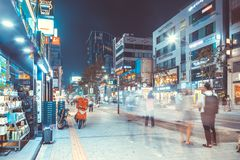 SEOUL, KOREA - AUGUST 12, 2015: Different people walking by opened stores at busy main street of Sinchon district at night - Seoul. SEOUL, KOREA - AUGUST 12 Stock Photography