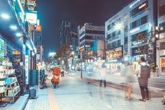 SEOUL, KOREA - 12. AUGUST 2015: Verschiedene Leute, die durch geöffnete Speicher an der beschäftigten Hauptstraße von Sinchon-Bez Stockfotografie