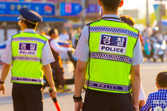 Seoul Policemen Vest Backs Street Demonstration. Seoul, South Korea - May 16, 2015: Rear of two Korean policemen in bright vest uniform, written police on back Stock Images