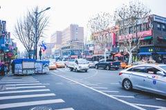 SEOUL, SÜDKOREA - 29. Dezember 2014: Verkehrsreiche Straße mit Autos und verschiedenen Shops in Ittaewon Stockfoto