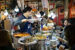 Vendor serving customers in Gwangjang Food Market. Seoul, South Korea - April 08, 2017: Woman vendor serving customers at Gwangjang Market in Seoul. It's one Royalty Free Stock Photo