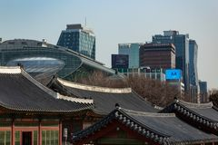 SEOUL, SOUTH KOREA - JAN 21, 2018: Deoksugung building roofs and modern Korean skyline, old and new contrast concept. SEOUL, SOUTH KOREA - JAN 21, 2018 royalty free stock photos