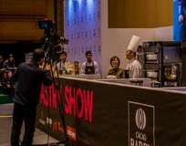 Camera man filming pastry show. Seoul, South Korea, January, 19, 2018: Camera man filming pastry show at the Seoul Salon of Chocolate exhibition at COEX Mall Stock Image