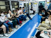 Seoul, South Korea - June 12, 2017: People sitting with mobile phones in the train in the Seoul subway royalty free stock images