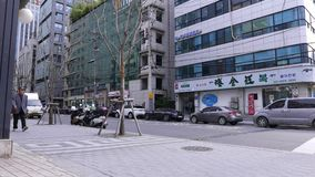Empty Seoul street, parked cars along road, pedestrians pass by