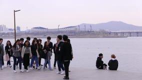 Group of young students walk together along Han river, Seoul, South Korea. SEOUL, SOUTH KOREA - MARCH 28 2018: Group of young students walk together along Han stock video