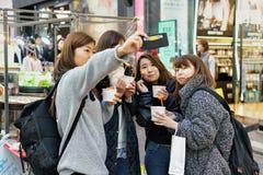 Korean girls tasting street food in Myeongdong market Seoul Stock Photos