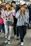 Korean girls tasting street food on Myeongdong market in Seoul Royalty Free Stock Photos