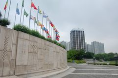 South Korea Olympic Park summer games with global flags flying on a cloudy day with the Olympic Plaque on the concrete ti royalty free stock photo