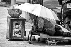 Seoul South Korea street, a crippled beggar under umbrella. Seoul South Korea, black and white image of an elderly man, crippled beggar lying under an umbrella Royalty Free Stock Photo