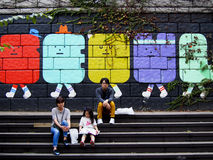 Seoul Street Art. People pause for a rest in front of some street art in downtown Seoul Stock Image