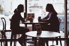 SEOUL SYDKOREA - AUGUSTI 10, 2015: Två asiatiska seende damer som dricker kaffe i en coffee shop - Seoul, Sydkorea Royaltyfri Bild