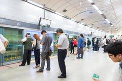 SEOUL SYDKOREA - MARS 28, 2017: Folk som står i linjen på en gångtunnelplattform och väntar på deras drev för att komma - Seoul, Royaltyfri Fotografi