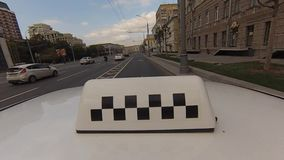 The taxi car is on street of Moscow. SEP 03, 2017, MOSCOW, RUSSIA: The taxi car is on street of Moscow. Taxi checkers. Shot of top light box or checkers on taxi stock video footage