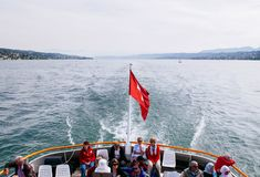 Tourists on cruise ship with Swiss flag in lake Zurich stock images