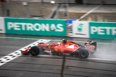 SEPANG - 29 MARS : Kimi Räikkönen conduisant la ligne d'arrivée sous la pluie Images libres de droits