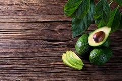 Separação do abacate ao meio na tabela de madeira velha com espaço livre para seu texto Fotos de Stock