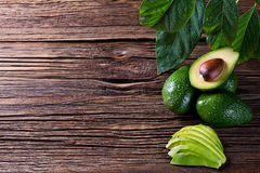 Separação do abacate ao meio na tabela de madeira velha com espaço livre para seu texto Fotografia de Stock