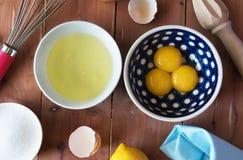 Separação a gema do ovo em pouca bacia e e da preparação para bater das claras de ovos e das gemas foto de stock royalty free