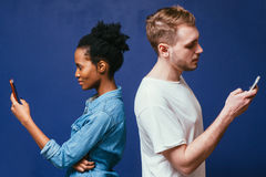 Separat folk för teknologi Man kvinna med telefonen arkivfoton