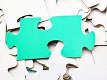 Separat grönt stycke på högen av vita pussel Arkivbild