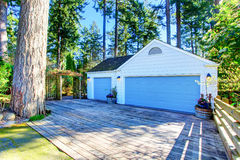 Separate garage with blue door and wooden driveway. Royalty Free Stock Images