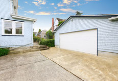Separate garage with blue and white trim and driveway. Royalty Free Stock Images