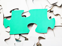 Separate green piece on pile of white jigsaw puzzles Stock Photography