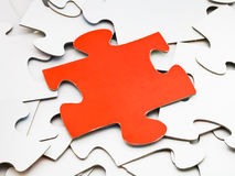 Separate red piece on pile of white jigsaw puzzles Royalty Free Stock Images