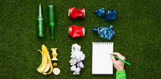 Separate waste collection. Waste sorting and separate garbage collection concept, tidy rubbish on the grass divided by material and man writing on a notepad, top Stock Photo