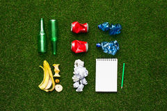 Separate waste collection. Waste sorting and separate garbage collection concept, tidy rubbish on the grass divided by material and a notepad, top view Stock Images