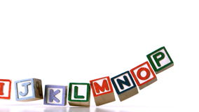 Separated alphabet blocks falling over Royalty Free Stock Images