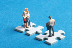 Separated, divorced. Two plastic figures standing on two puzzle pieceswith a hole in it, they are split Stock Images