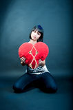 Separated heart. Young sad caucasian girl with dark hair sitting on floor with heart pillow separated with rope isolated over gray background Royalty Free Stock Photography