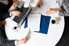 Separated job. Human hands holding pens and papers, making notes in documents, typing on the lap top placed on the table with two cups of coffee on it Stock Photos