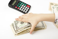 Separating. Hand separating dollars by type on white background and a black calculator Royalty Free Stock Image